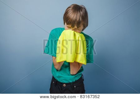 European-looking boy of ten years is ill, a handkerchief on a gr