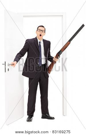Full length portrait of a man with rifle standing by a door isolated on white background