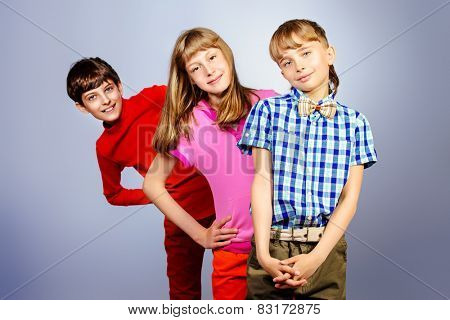 Three friends teenagers standing together. Studio shot.