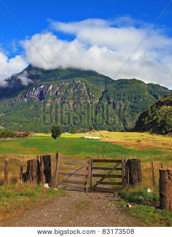 Rural areas in the Chilean Patagonia. The field is fenced with a low strong fence. On the horizon mountain overgrown with the wood