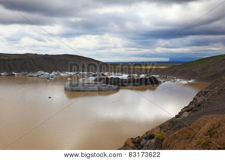 Ice covered with volcanic ash. Mirror Lake, formed as a result of thawing of a glacier Vatnaj�?�¶kull glacier spurs. Iceland in July. Skaftafell National Park