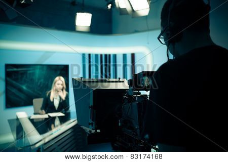 Young beautiful blonde television announcer at studio during live broadcasting
