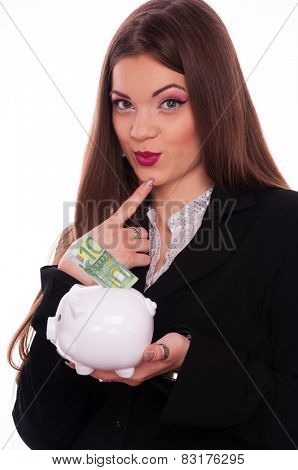 Conceived young brunette put hundred Euro bill in the piggy bank, on white background