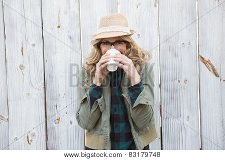 Portrait of blonde drinking from disposable cup against bleached wooden planks