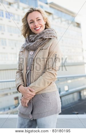 Happy blonde in warm clothes posing in the city