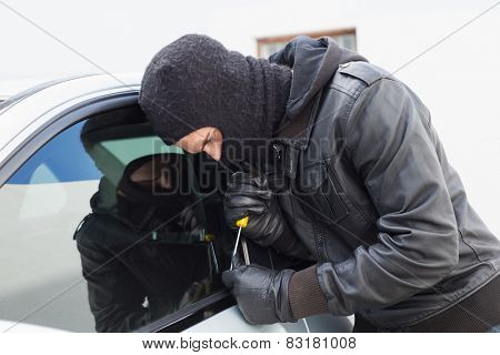 Thief breaking into a car in broad daylight