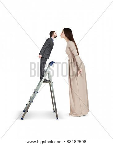 beautiful young woman raising forward and kissing small man on stepladder. isolated on white background