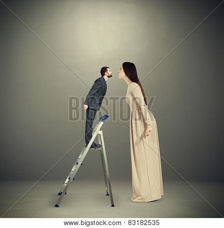 beautiful young woman kissing small man on stepladder. concept photo over dark background