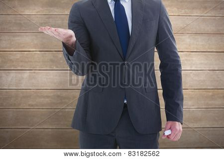 Businessman holding hand out in presentation against wooden surface with planks