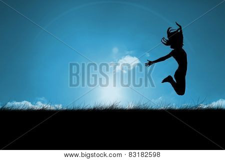 Silhouette of woman jumping against blue sky over grass