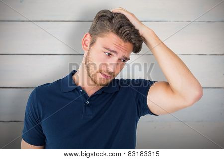 Handsome young man looking confused against painted blue wooden planks