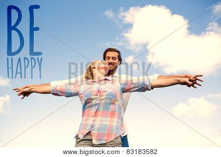 Happy couple standing outside with arms stretched kissing against be happy
