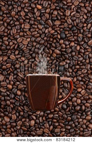 A mug of steaming hot coffee on a background of fresh roasted beans. Vertical format with copy space.