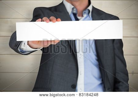 Businessman in grey suit showing card against bleached wooden planks background