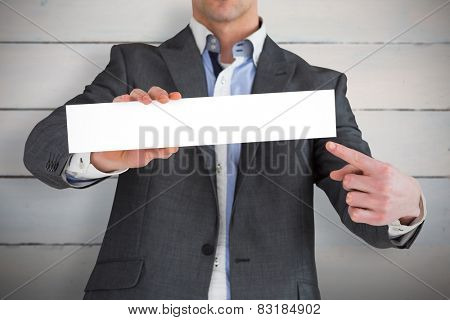 Businessman in grey suit showing card against painted blue wooden planks