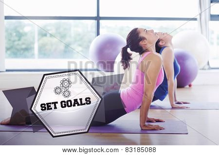 The word set goals and fit women doing the cobra pose in fitness studio against hexagon