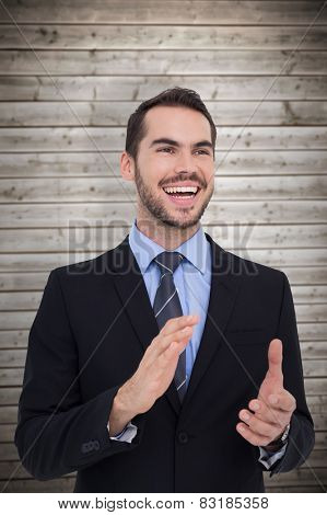 Happy businessman standing and clapping against wooden planks background