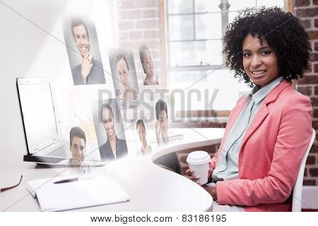 Happy casual businesswoman sitting at desk against profile pictures