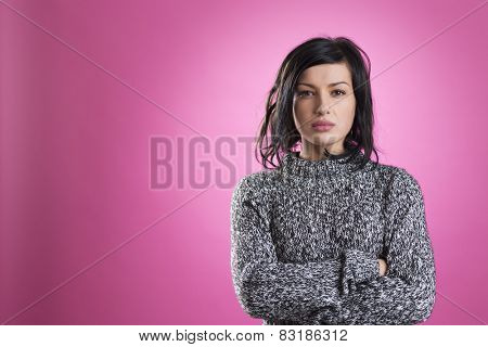 Young unhappy woman with messy hair and crossed arms looking annoyed, isolated on pink background.
