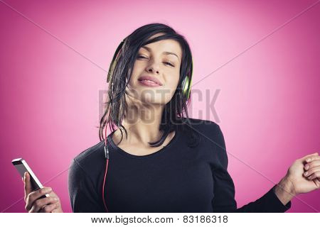 Smiling happy girl enjoying listening to music with earphones and mp3 player while dancing, isolated on pink background.
