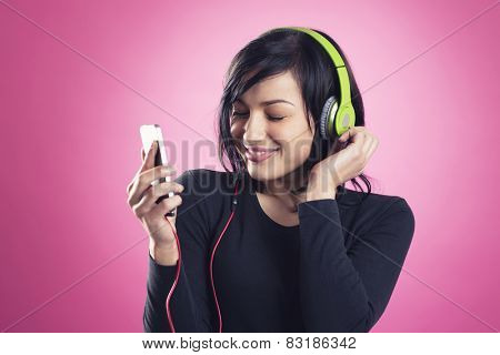 Smiling happy girl enjoying listening to music with headphones and mp3 player with eyes closed, while dancing, isolated on pink  background.