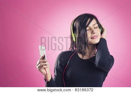 Happy smiling girl listening to music with headphones and mp3 player with eyes closed, in calm and relaxed mood, isolated on pink background.
