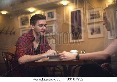 Couple is having a date in cafe. They drink coffee tea and talk to each other.