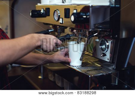 Young man is making fresh coffee with coffeemachine.