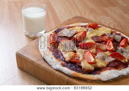 Closeup Of Homemade Pizza With Tomato, Bacon, Salami And Cheese. Wooden Cutting Board. Cup Of Milk O
