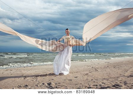 Incredible Portrait Of Model With Extremely Long Dress At The Beach. Outdoors