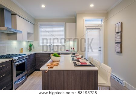 Modern kitchen interior with island and cabinets in a luxury house set for dinner