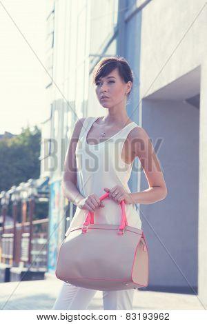Model Holding Handbag Outdoor.beige Blouse. White Shirt. Beige Leather Bag. High Heels