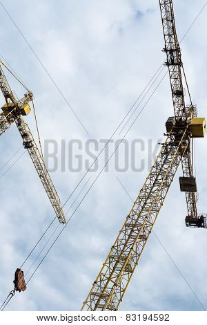 Tower Cranes Against The Cloudy Sky