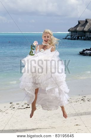 The beautiful woman with a rose jumping on the edge of the sea on a beach. Polynesia.