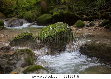Moss overgrown stone in the stream