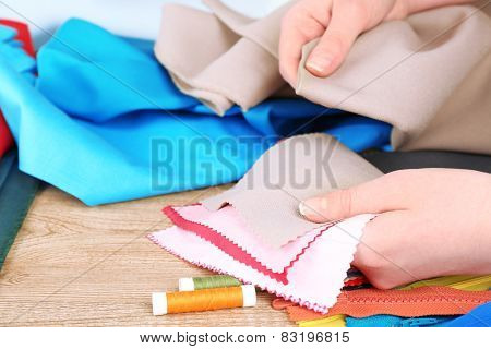 Colorful fabric samples in female hands on wooden table background
