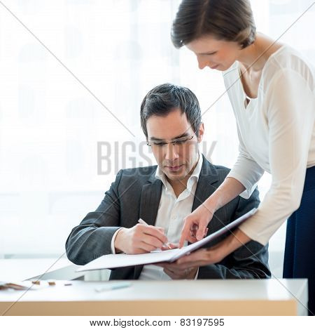 Businessman Signing A Document Hold By Secretary