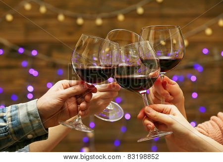 Clinking glasses of red wine in hands on bright lights background