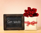 stock photo of get well soon  - Get Well message written on little chalkboard with roses and present box - JPG