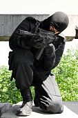 picture of extremist  - Terrorist aiming his target with a gun standing on his knee - JPG