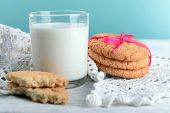 picture of milk glass  - Tasty cookies and glass of milk on color wooden background - JPG