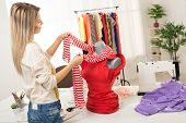 stock photo of dress mannequin  - Young woman fashion designer creates a dress on mannequin - JPG