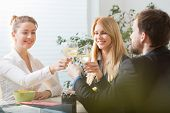 stock photo of assemblage  - Three young businesspeople toasting on a lunch - JPG