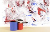 image of untidiness  - Partly finished untidy or messy blue and red painted wall with paint cans and paintbrushes - JPG