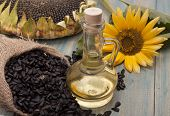 foto of sunflower  - Sunflower oil in a glass jug sunflower seeds and flower on a blue table - JPG