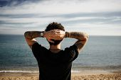 stock photo of boys  - Caucasian boy on beach standing in sand with hands behind head and looking at ocean enjoying sun and summer travel holidays vacation getaway in Spain - JPG