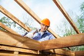 picture of timber  - Low angle view of male worker hammering nail on incomplete timber cabin at site - JPG