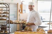 pic of trays  - Smiling baker holding tray of bread in the kitchen of the bakery - JPG