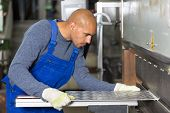 stock photo of bend  - Worker operating a machine for bending sheet metal