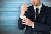 pic of cuff  - Handsome businessman adjusting his cuffs against wooden planks - JPG